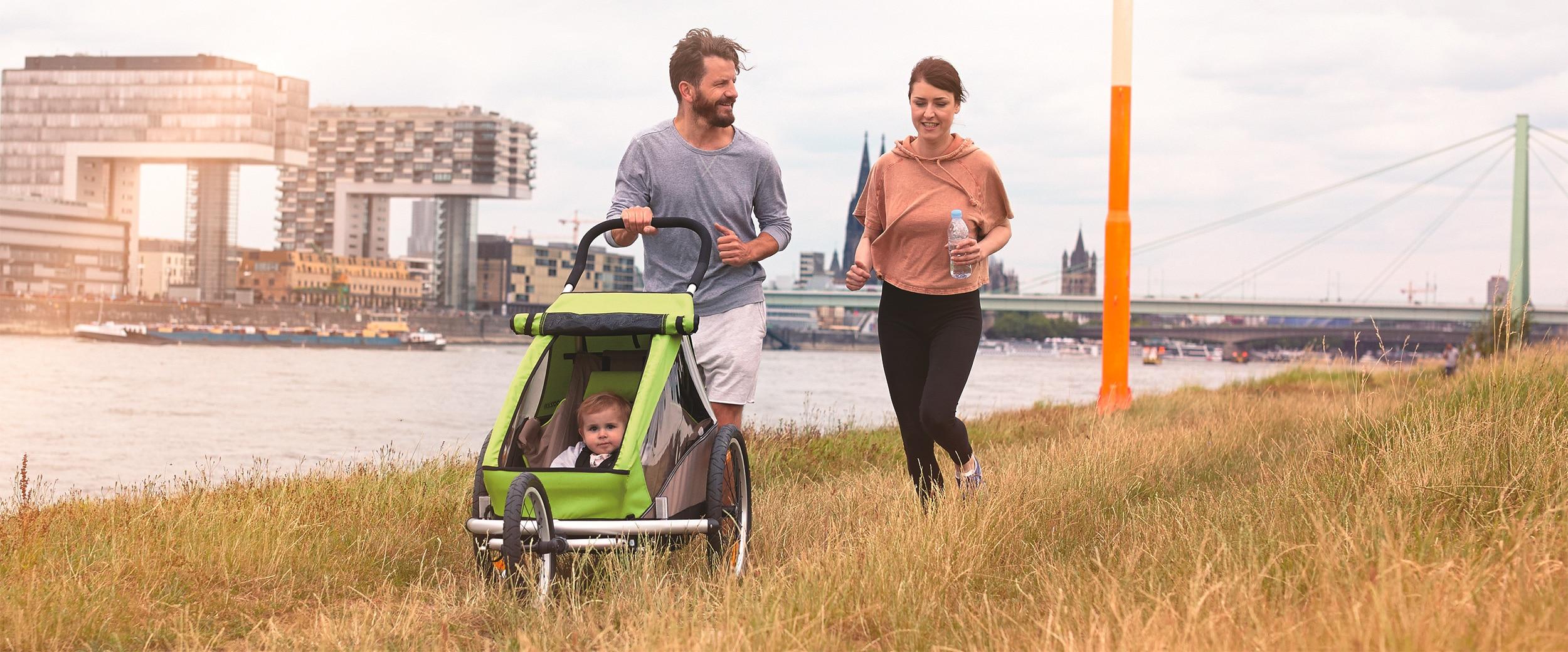 Pärchen geht am Rhein in Köln mit Kind im Croozer spazieren.