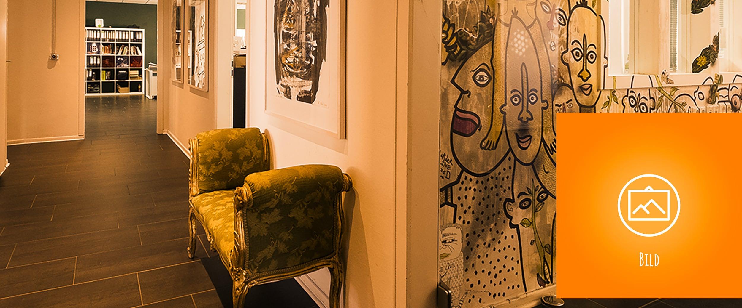 Ein grünes Barock-Sofa vor einer Wand mit Streetart.