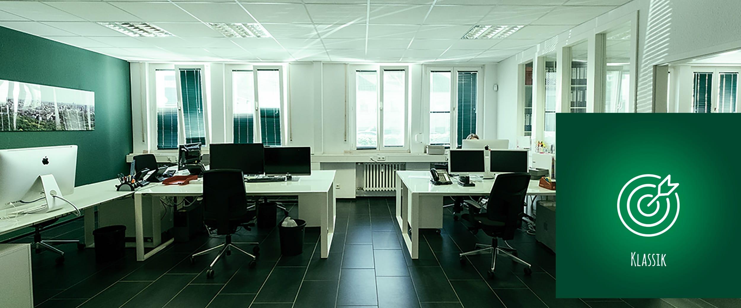 Büroraum mit schwarzen Fliesen, weißen und schwarzen Möbeln und grünen Akzenten.