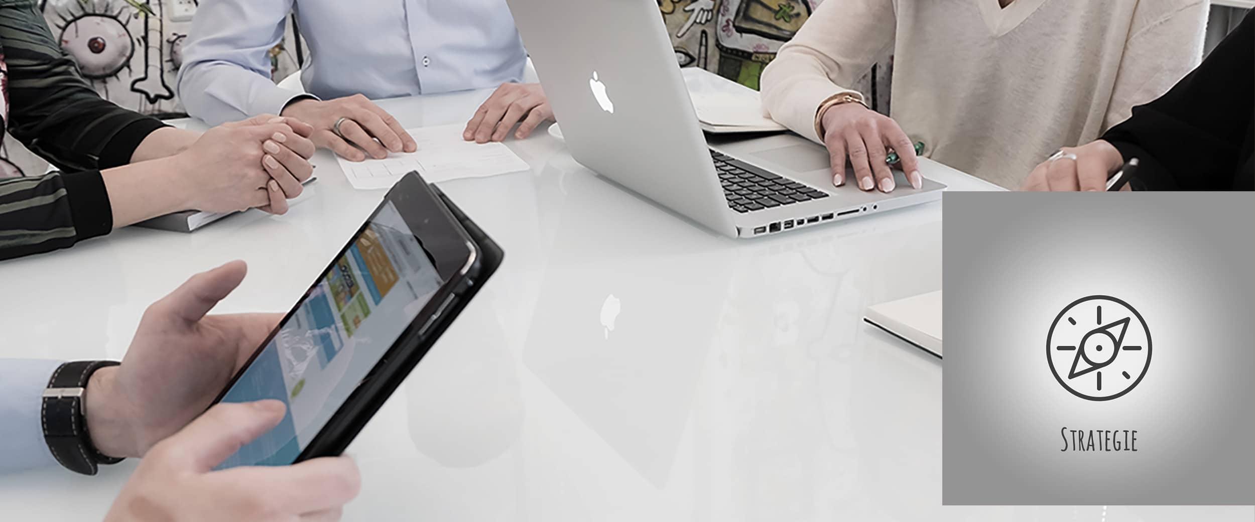 Weißer Glastisch, auf dem Laptops stehen und die Hände von Mitarbeitern zu sehen sind.
